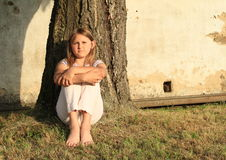 Menina triste que senta-se pelo tronco Fotos de Stock Royalty Free