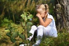 A menina triste só em um vestido branco e em uma flor em sua mão foi perdida nas madeiras, sentando-se perto de uma árvore e grit fotografia de stock royalty free