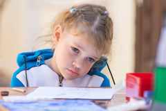 A menina triste senta-se em uma tabela no pátio da casa e não se quer tirar Imagem de Stock Royalty Free