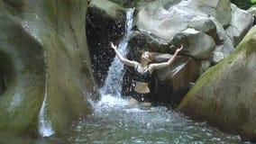 Menina ttractive do  de Ð no movimento lento que espirra a água clara do lago e dos olhares da montanha à câmera com a cachoeira vídeos de arquivo