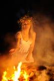 Menina ucraniana com uma grinalda das flores em sua cabeça contra vagabundos Imagens de Stock Royalty Free