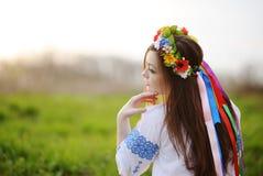 A menina ucraniana em uma camisa e uma flor envolvem-se em sua cabeça em um b Foto de Stock Royalty Free