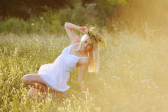 Menina ucraniana no sundress brancos com uma grinalda das flores em h Fotos de Stock
