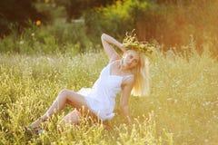 Menina ucraniana no sundress brancos com uma grinalda das flores em h Imagens de Stock
