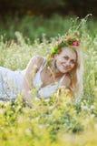 Menina ucraniana no sundress brancos e uma grinalda das flores sobre ele Imagens de Stock Royalty Free