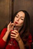 A menina ucraniana nova e bonita é cocktail vermelho bebendo 'sexy' do batido imagem de stock
