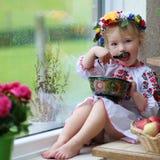 Menina ucraniana pequena no vestido nacional com alimento tradicional fotografia de stock royalty free