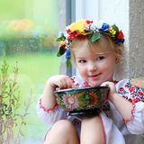 Menina ucraniana pequena no vestido nacional com alimento tradicional imagem de stock royalty free