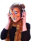 A menina um tigre nos auriculares escuta música. Imagem de Stock