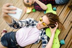 Menina urbana à moda nova no equipamento do moderno que faz o selfie ao encontrar-se com no cais de madeira fotos de stock royalty free