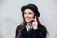 A menina urbana de sorriso usa o telefone esperto com sorriso em sua cara O retrato do gir elegante que veste um estilo do preto  Fotos de Stock