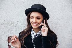 A menina urbana de sorriso usa o telefone esperto com sorriso em sua cara O retrato do gir elegante que veste um estilo do preto  Imagens de Stock