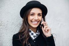 A menina urbana de sorriso usa o telefone esperto com sorriso em sua cara O retrato do gir elegante que veste um estilo do preto  Fotos de Stock Royalty Free