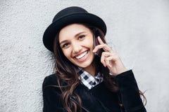 A menina urbana de sorriso usa o telefone esperto com sorriso em sua cara O retrato do gir elegante que veste um estilo do preto  Fotografia de Stock
