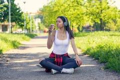 Menina urbana desportiva que senta-se no skate e na m?sica de escuta Fora, estilo de vida urbano fotografia de stock