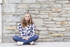 Menina urbana que senta-se na rua e que olha a câmera fotografia de stock royalty free
