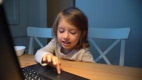 A menina usa entusiasticamente o portátil que senta-se em uma tabela Tiro da zorra video estoque