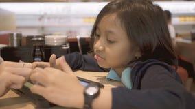 A menina usa o telefone celular no café vídeos de arquivo