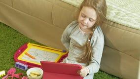 A menina usa uma tabuleta do computador no interior video estoque