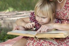 A menina vê algo nos livros que caracterizam a mamã Foto de Stock