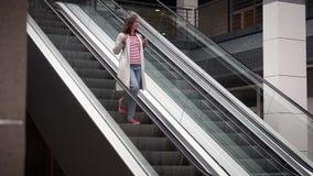 A menina vai abaixo da escada rolante na loja filme