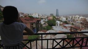 A menina vai ao balcão com ideia da parte velha Tbilisi, Geórgia, telhados das construções, arranha-céus de vidro vídeos de arquivo