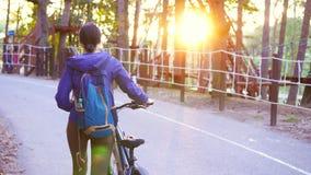 A menina vai com a bicicleta no parque no por do sol vídeos de arquivo