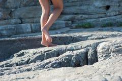 A menina vai com os pés descalços nas rochas, escalando acima fotos de stock