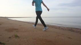 A menina vai no trote de movimento ao longo da praia no nascer do sol