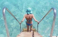 A menina vem em baixo na água azul Fotos de Stock Royalty Free