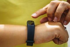 A menina verifica o pulso no podômetro do bracelete da aptidão ou do perseguidor da atividade no pulso fotografia de stock royalty free