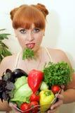 Menina vermelha com os vegetais nas mãos Foto de Stock