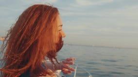 Menina vermelha do cabelo no barco de motor do boi do vestido de turquesa Por do sol bonito noite vídeos de arquivo
