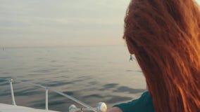 Menina vermelha do cabelo no barco de motor do boi do vestido de turquesa Por do sol bonito romântico filme