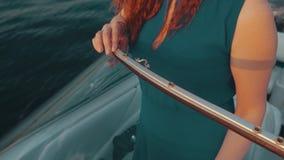 Menina vermelha do cabelo no barco de motor do boi do vestido de turquesa Por do sol do verão romântico filme