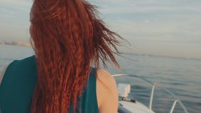 Menina vermelha feliz do cabelo no barco de motor do boi do vestido de turquesa Por do sol bonito filme