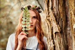 Menina vermelha misteriosa do cabelo na madeira com folha Imagens de Stock