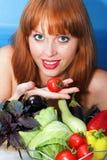 A menina vermelha prende um tomate Foto de Stock