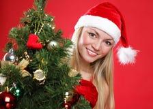 Menina vestida como Santa e uma pele-árvore do Natal foto de stock