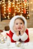 Menina vestida como Santa pela chaminé Imagens de Stock Royalty Free