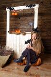 A menina vestida como uma bruxa senta-se em uma abóbora O conceito de Dia das Bruxas Imagem de Stock
