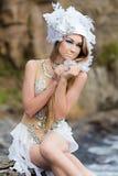 A menina vestida como uma sereia está sentando-se na praia Imagem de Stock