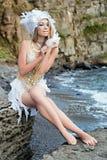 A menina vestida como uma sereia está sentando-se na praia Foto de Stock