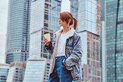 Menina vestida na moda do moderno com tatuagem em sua cara que guarda o café afastado na frente dos arranha-céus na cidade de Mos fotos de stock royalty free
