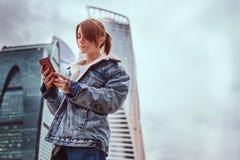 Menina vestida na moda do moderno com tatuagens em suas cara e mão usando um smartphone na frente dos arranha-céus na cidade de M fotos de stock