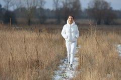 Menina vestida nas caminhadas brancas no campo fotos de stock