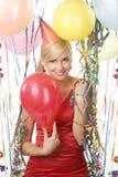 Menina vestida vermelha no partido com balões fotografia de stock royalty free