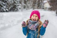 A menina vestiu-se em um revestimento azul e em gritar de gracejo do chapéu cor-de-rosa no inverno Fotografia de Stock