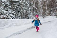 A menina vestiu-se em um revestimento azul e um chapéu cor-de-rosa e as botas, divertimento correm através da floresta do inverno Fotos de Stock Royalty Free