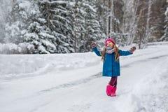A menina vestiu-se em um revestimento azul e um chapéu cor-de-rosa e botas, hamming e jogo na floresta do inverno Imagens de Stock Royalty Free